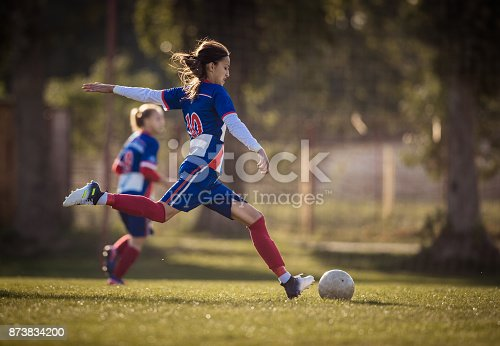 Teenage girl running with soccer ball on a playing field during the match and about to kick the ball.