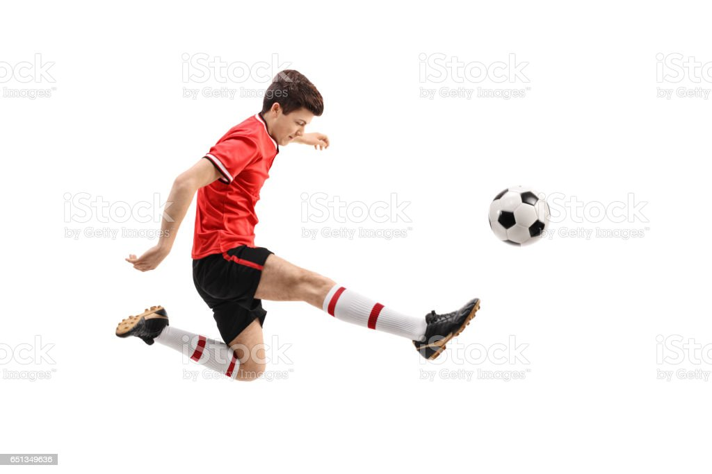 Teenage soccer player kicking a football stock photo