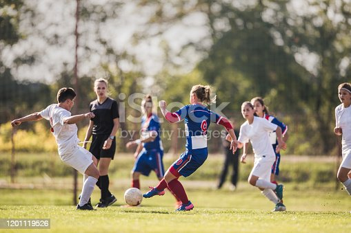 Determined female soccer player in action during the match on playing field.
