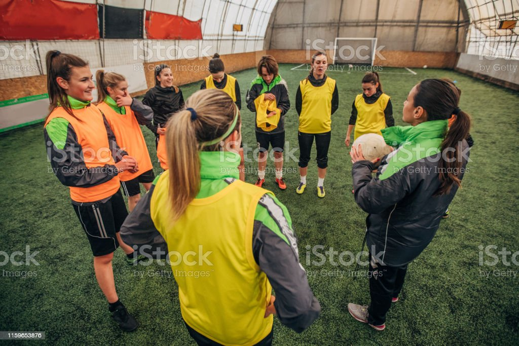 Teenage girl soccer team on indoor sport court with grass talking...
