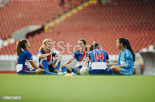 Happy female soccer players talking while sitting on grass after sports training. Copy space.