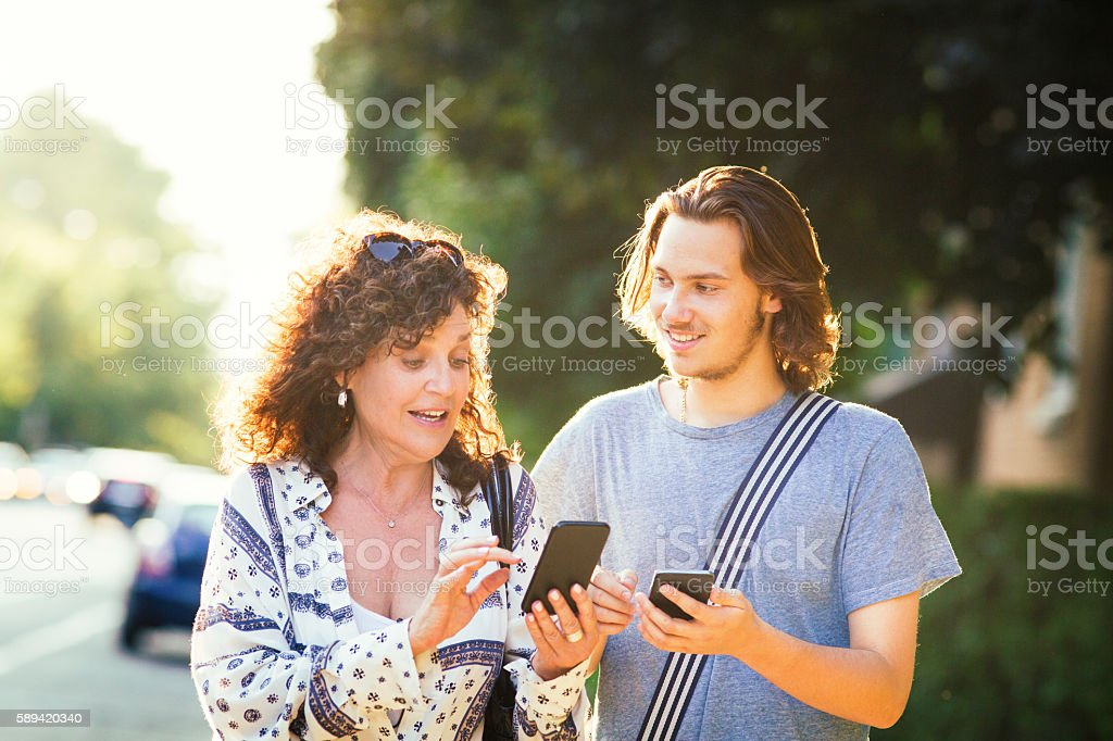 Teenage son explains smart phone game to his mother stock photo