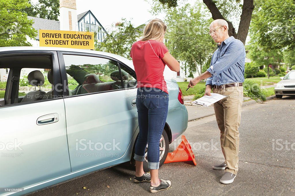 Teenage Student Driver Making Error in Driving Examination with Examiner royalty-free stock photo