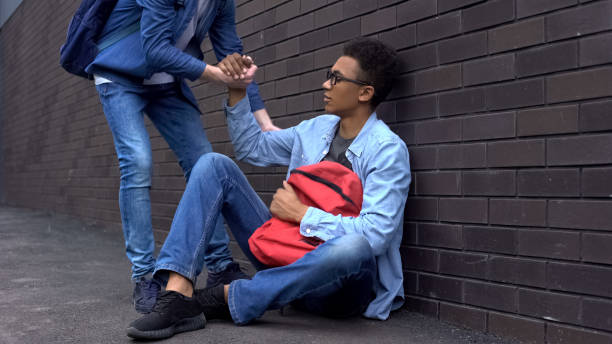 Teenage student giving helping hand to bullied afro-american boy, stop racism Teenage student giving helping hand to bullied afro-american boy, stop racism social justice concept stock pictures, royalty-free photos & images