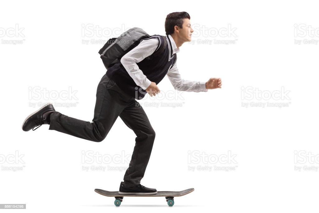 Teenage student riding a skateboard stock photo