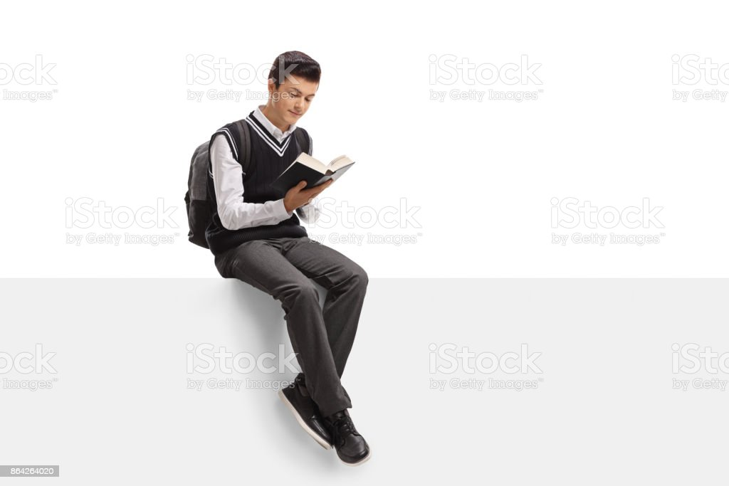 Teenage student sitting on a panel and reading a book royalty-free stock photo