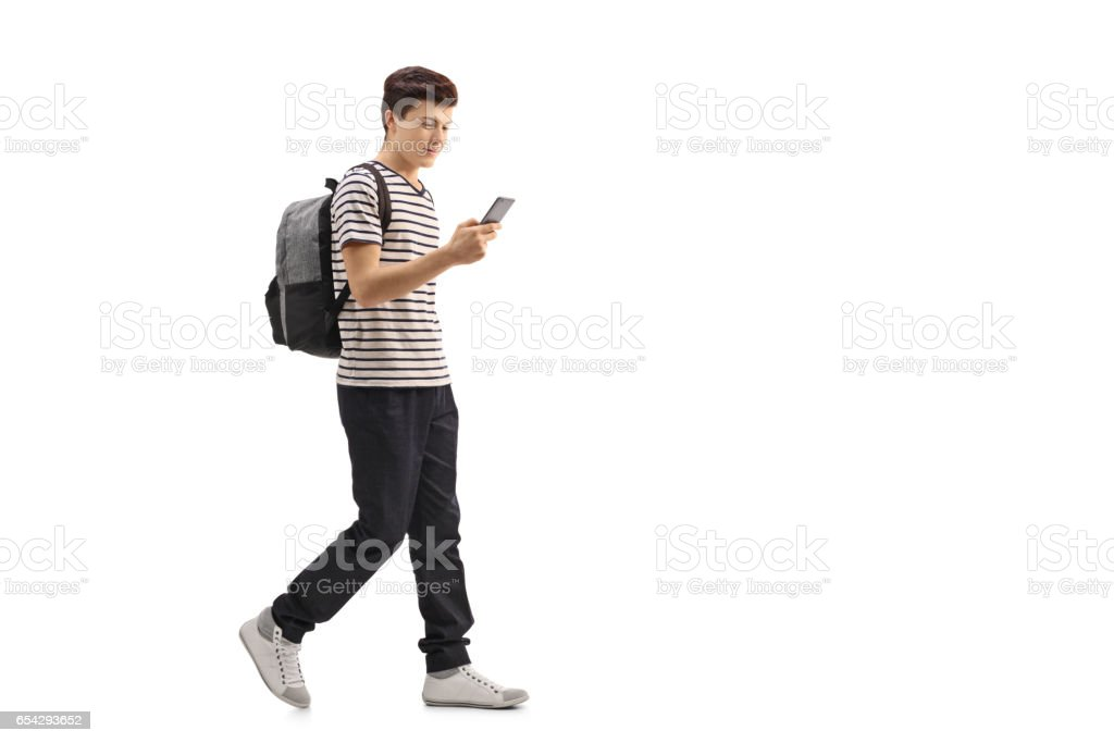 Teenage student walking and looking at a phone stock photo
