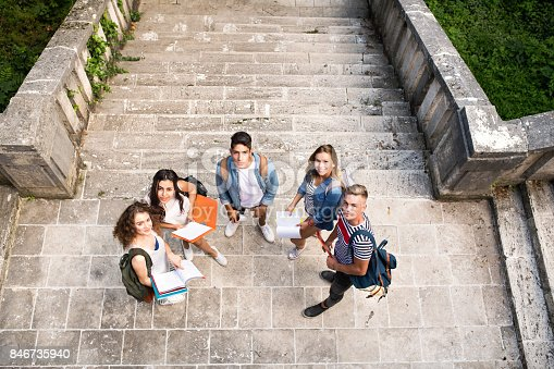 824257318 istock photo Teenage students at the stone steps in front of university. 846735940