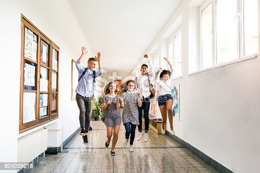 824257318 istock photo Teenage students in high school hall jumping high. 824255018