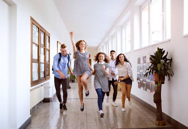 teenage students in high school hall jumping high. - compagni scuola foto e immagini stock