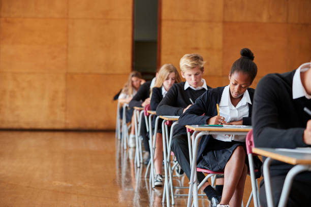 teenage students in uniform sitting examination in school hall - private school stock photos and pictures