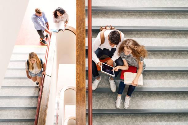 teenage students on stairs in high school. - compagni scuola foto e immagini stock