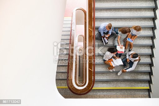824257318 istock photo Teenage students on stairs in high school. 861713042