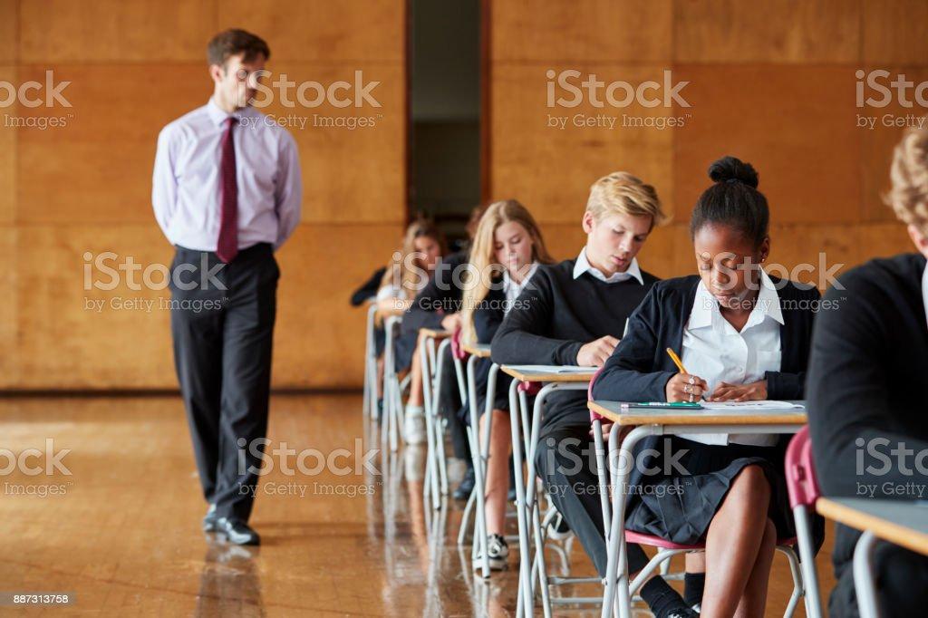Estudiantes adolescentes sentado examen con profesor Invigilating - foto de stock