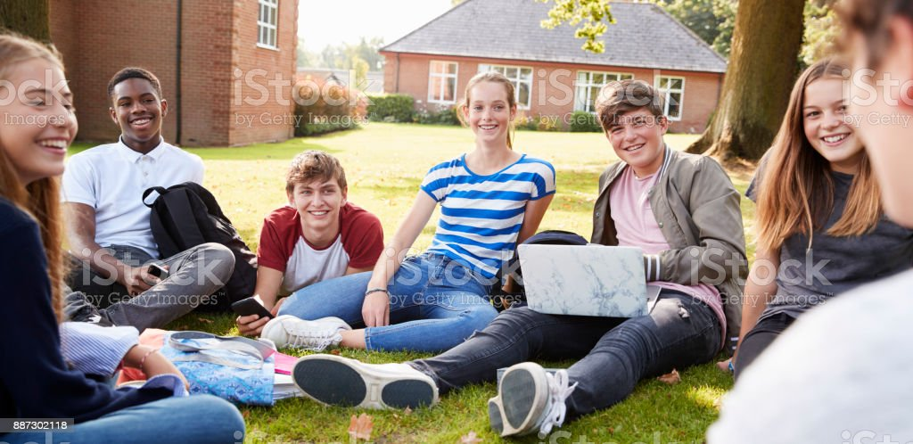 Teenage Students Sitting Outdoors And Working On Project stock photo