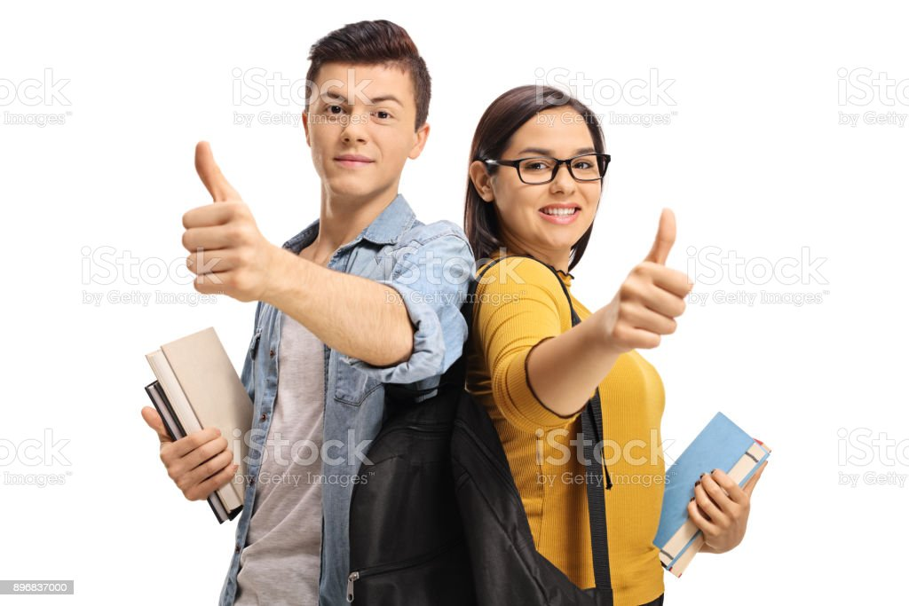 Teenage students with backpacks and books making thumb up gestures stock photo