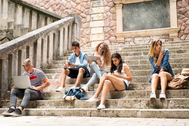 jugendlichen studenten mit gadgets außerhalb auf steinernen stufen. - suche freundin stock-fotos und bilder