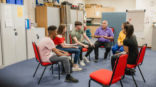 Teenage Support Group Small group of teenagers are talking in a support group with a mature mental health professional. community center stock pictures, royalty-free photos & images