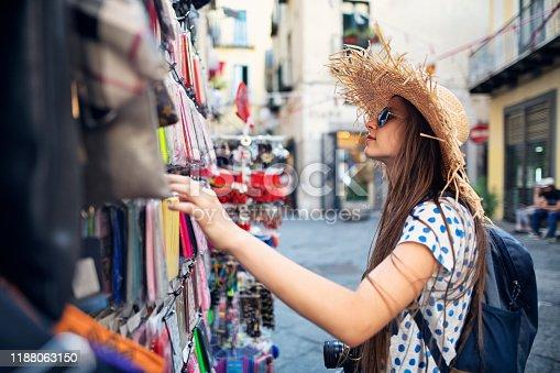 Teenage girl buying smartphone case at street shop. Nikon D850