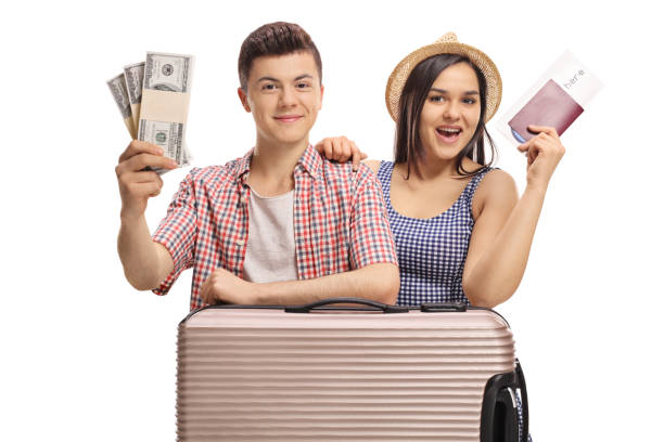 Teenage tourists with bundles of money and a passport stock photo