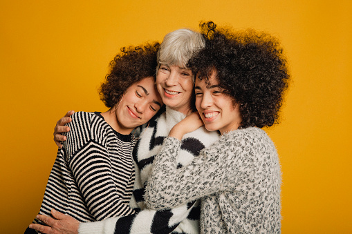 Mid-length portrait of two teenage female twins and their mature mother embracing in front of a yellow background.