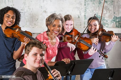 A group of four multi-ethnic teenagers in music class with their teacher, practicing on string instruments. The of the students are holding violins and the fourth is a double bass player. They are smiling at the camera.