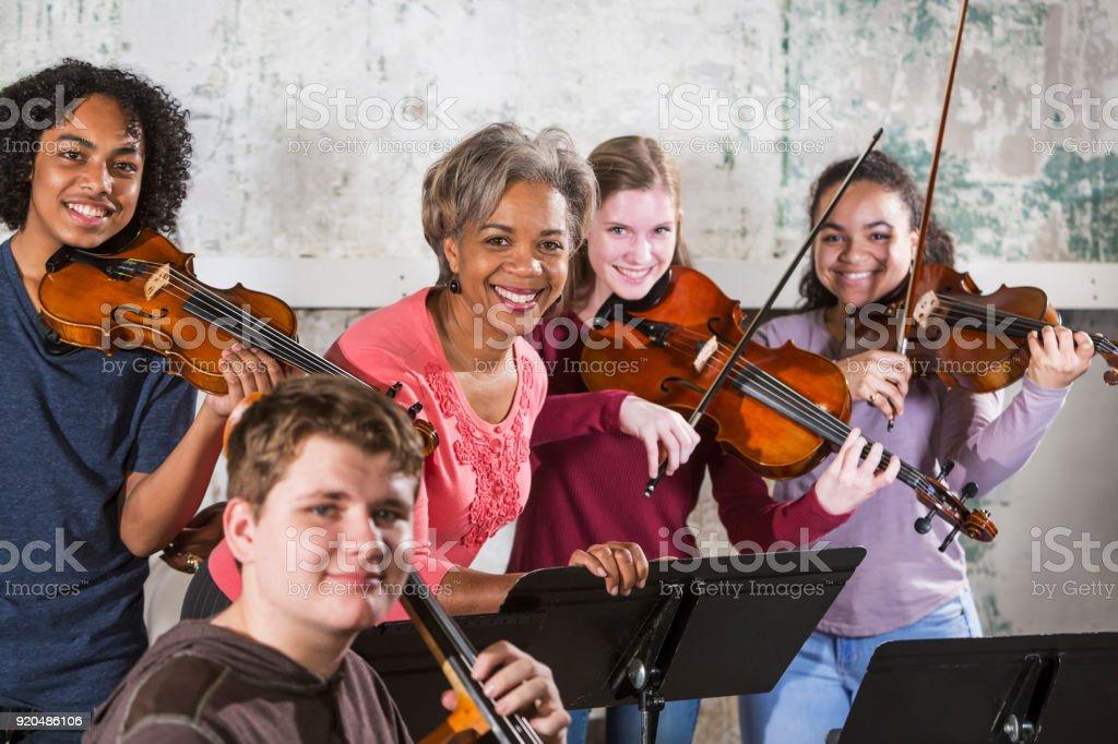 Teenage violinists with music teacher stock photo