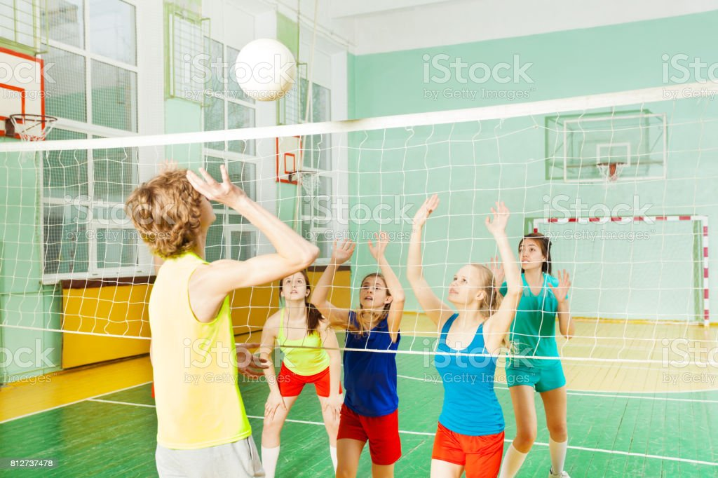 Teenage volleyball player serving ball overhand stock photo