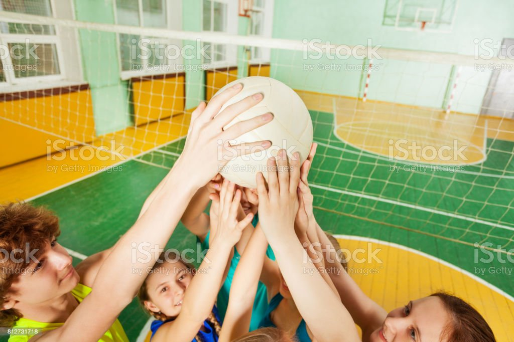 Teenage volleyball team players serving a ball stock photo