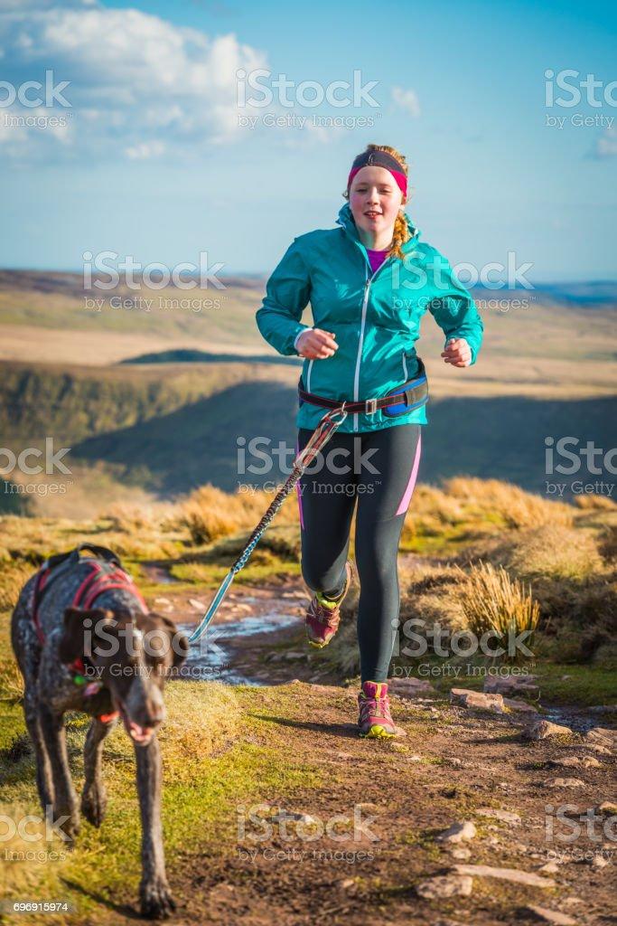 Teenage woman trail running on mountain path with canicross dog stock photo