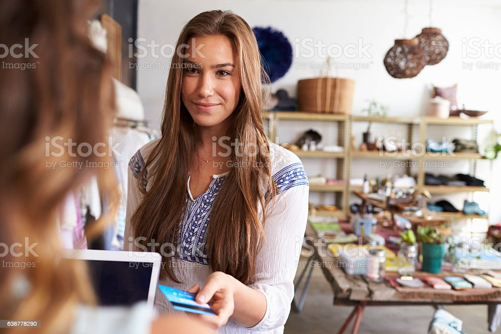 Teenage young woman paying with credit card in a boutique stock photo