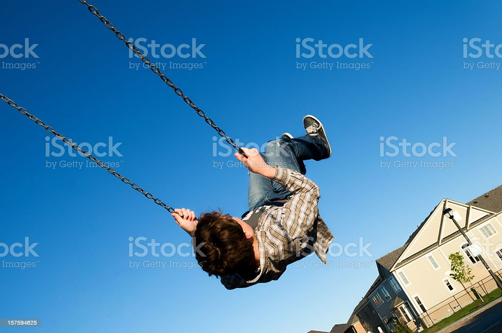 Teenaged Boy Swinging in Suburban Playground royalty-free stock photo