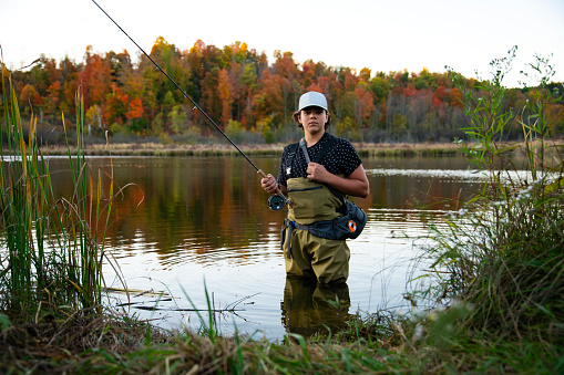 A young fly fisherman wading in a lake on a beautiful autumn day.