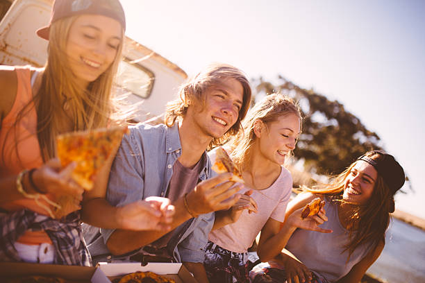 teenaged freunde sitzen zusammen essen pizza - teenage friends sharing food stock-fotos und bilder