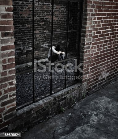A young teenaged girl - perhaps a runaway - is huddled alone at night behind a grungy brick wall in an abandoned urban building.