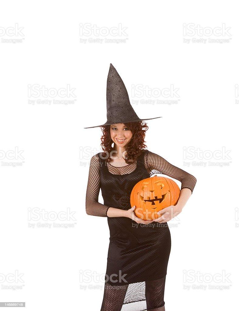 Teenaged girl in Halloween costume with pumpkin(focus on pumpkin royalty-free stock photo