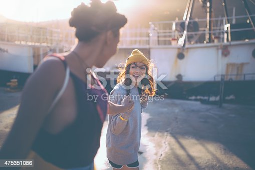 Teenaged girl friends in grunge styling holding hands while walking around a harbour on a summer afternoon