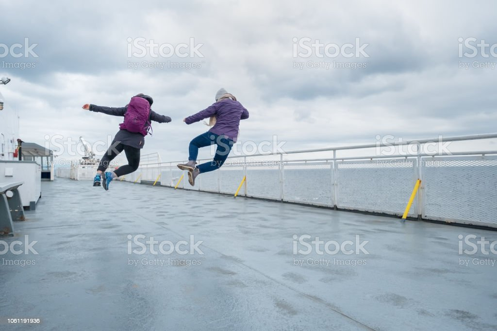 Teenaged Sisters Jumping in Unison on Ferry Deck, Canada stock photo