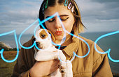 A teenager by the sea holding a puppy, photographed with Kono Luft 35mm film and heart effects.