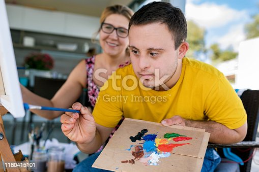 Teen boy with Down syndrome painting on canvas with his tutor    on terrace above riverbank
