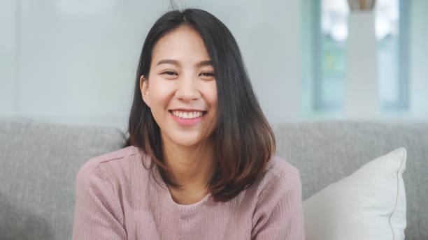 Teenager asiatische Frau das Gefühl glücklich lächelnd und Blick auf die Kamera, während im Wohnzimmer zu Hause entspannen. Lifestyle schöne asiatische junge Frau mit Entspannung Zeit zu Hause Konzept. – Foto