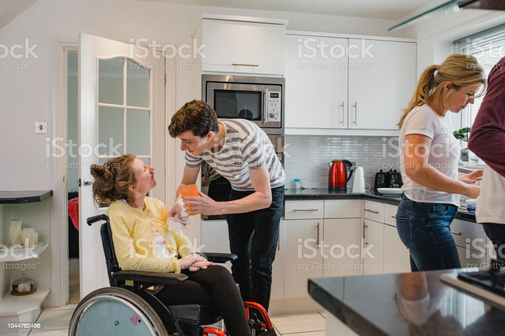 Teenager Assisting his Disabled Sister in the Kitchen stock photo
