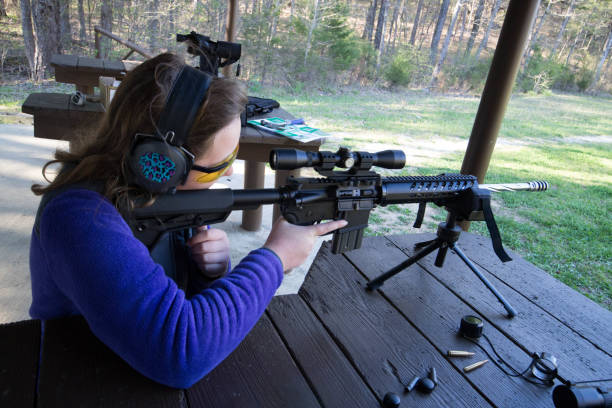 Teenager at shooting range Teenage Girl at the shooting range firing a rifle. ar 15 stock pictures, royalty-free photos & images