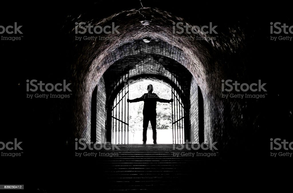 Teenager at the end of a dark tunnel stock photo