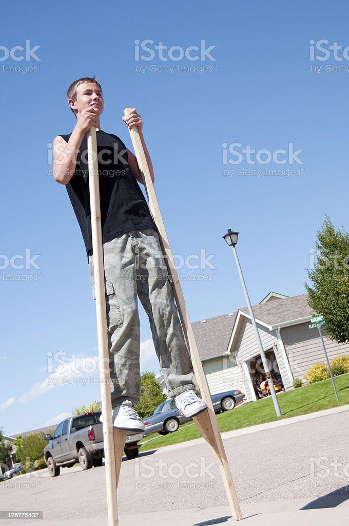 Teenager balancing on stilts royalty-free stock photo