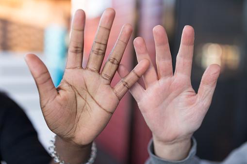 istock Teenager black hand and woman white hand 965705288