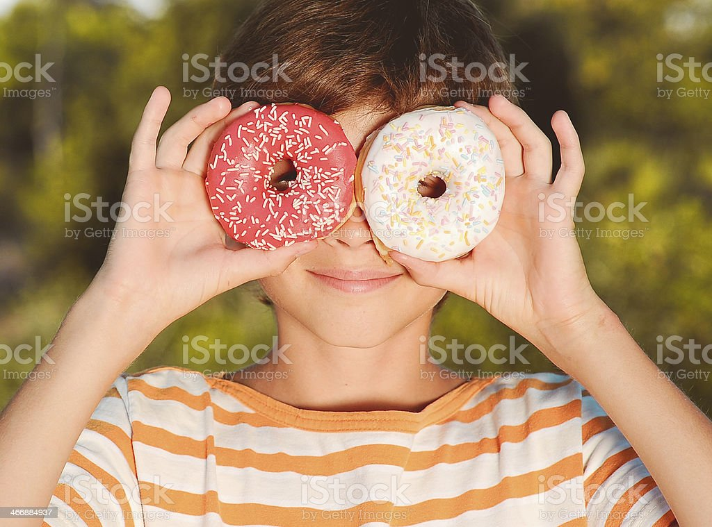 Teenager boy having fun with donuts royalty-free stock photo