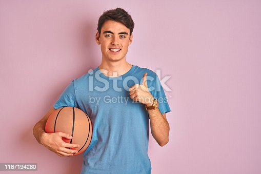 istock Teenager boy holding professional basket ball over isolated pink background happy with big smile doing ok sign, thumb up with fingers, excellent sign 1187194260