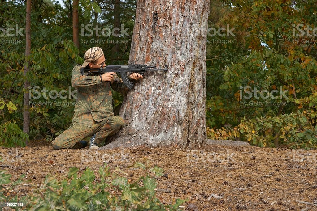 Teenager, boy in battle dress and a rifle royalty-free stock photo