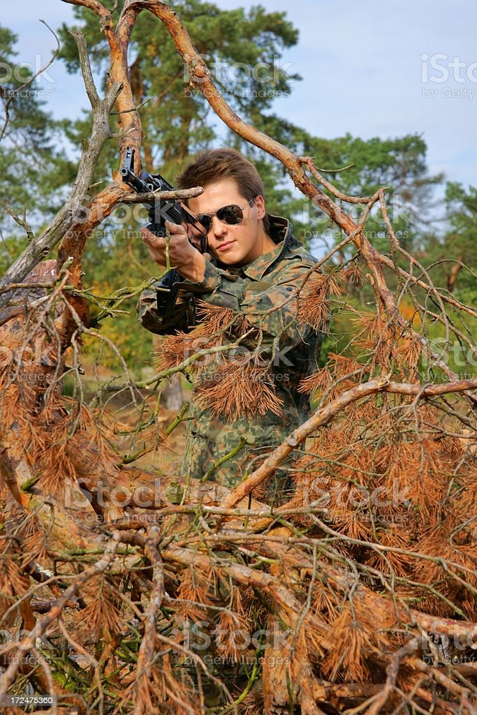 Teenager, boy in battle dress and a rifle stock photo
